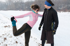 Άνδρας και γυναίκα που θερμαίνουν πριν από να τρέξει έξω στο χιόνι Στοκ Εικόνες