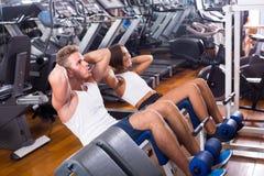 Άνδρας και γυναίκα που κάνουν να καθίσει το UPS που χρησιμοποιεί μαζί τη μηχανή στη γυμναστική Στοκ Εικόνες