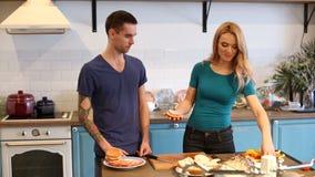 Άνδρας και γυναίκα που κατασκευάζουν τα χάμπουργκερ φιλμ μικρού μήκους