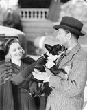 Άνδρας και γυναίκα που κρατούν ένα μικρό σκυλί (όλα τα πρόσωπα που απεικονίζονται δεν ζουν περισσότερο και κανένα κτήμα δεν υπάρχ στοκ εικόνες με δικαίωμα ελεύθερης χρήσης