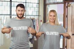 Άνδρας και γυναίκα που παρουσιάζουν εθελοντικό κείμενο στις μπλούζες στοκ εικόνες
