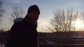 Άνδρας και γυναίκα που περπατούν μαζί σε μια μικρή γέφυρα ενάντια στον ήλιο το χειμώνα 4K steadicam πυροβολισμός, άποψη σχεδιαγρά απόθεμα βίντεο