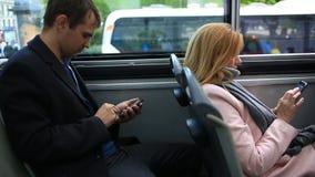 Άνδρας και γυναίκα που ταξιδεύουν με το λεωφορείο επίσκεψης τουριστών, με ένα έξυπνο τηλέφωνο απόθεμα βίντεο