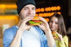 Άνδρας και γυναίκα που τρώνε burger Το νέο κορίτσι και ο νεαρός άνδρας κρατούν τα burgers σε ετοιμότητα Στοκ φωτογραφίες με δικαίωμα ελεύθερης χρήσης