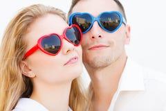 Άνδρας και γυναίκα που φορούν τα γυαλιά ηλίου μορφής καρδιών Στοκ Εικόνα