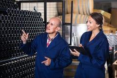 Άνδρας και γυναίκα σε ομοιόμορφο στο κελάρι κρασιού Στοκ Εικόνα