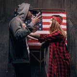 Άνδρας και γυναίκα σε σύγκρουση στο σκηνικό αμερικανικών σημαιών Στοκ Εικόνα