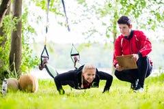 Άνδρας και γυναίκα στην ικανότητα που εκπαιδεύουν κάνοντας το ώθηση-UPS Στοκ Φωτογραφία