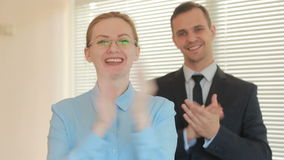Άνδρας και γυναίκα δύο επιχειρηματιών που χτυπούν σε ένα γραφείο σε ένα υπόβαθρο παραθύρων με τα παραθυρόφυλλα μήλων απόθεμα βίντεο