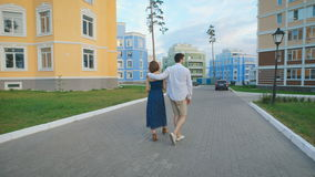 Άνδρας και γυναίκα strolling κατά μήκος της μοντέρνης κατοικήσιμης περιοχής απόθεμα βίντεο