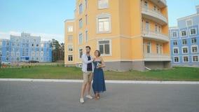 Άνδρας και γυναίκα strolling κατά μήκος της μοντέρνης κατοικήσιμης περιοχής φιλμ μικρού μήκους