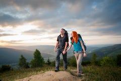 Άνδρας και κοκκινομάλλης γυναίκα στο δρόμο στα βουνά στοκ εικόνα