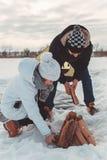 Άνδρας και τεθειμένο γυναίκα καυσόξυλο στο χιόνι για να ανάψει μια πυρκαγιά Στοκ Εικόνες