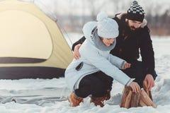 Άνδρας και τεθειμένο γυναίκα καυσόξυλο στο χιόνι Στοκ Φωτογραφία