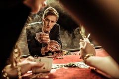 Άνδρας με τις κάρτες ποτών και πόκερ που εξετάζει τη γυναίκα στη χαρτοπαικτική λέσχη Στοκ Εικόνες