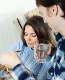 Άνδρας που δίνει sirup στην αδιάθετη γυναίκα Στοκ Εικόνα
