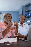 Άνδρας που εξετάζει την ιατρική καθμένος από τη γυναίκα που χρησιμοποιεί το φορητό προσωπικό υπολογιστή Στοκ εικόνα με δικαίωμα ελεύθερης χρήσης