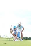 Άνδρας που εξετάζει τη γυναίκα που στοχεύει τη σφαίρα στο γήπεδο του γκολφ ενάντια στον ουρανό Στοκ εικόνα με δικαίωμα ελεύθερης χρήσης