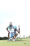 Άνδρας που εξετάζει τη γυναίκα που στοχεύει τη σφαίρα στο γήπεδο του γκολφ ενάντια στον ουρανό Στοκ φωτογραφία με δικαίωμα ελεύθερης χρήσης