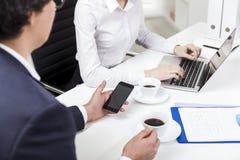 Άνδρας που εξετάζει το τηλέφωνό του, δακτυλογράφηση γυναικών στο γραφείο Στοκ φωτογραφία με δικαίωμα ελεύθερης χρήσης
