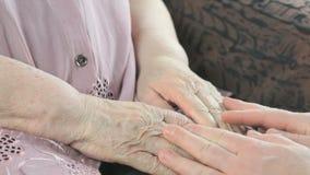 Άνδρας που κρατά τα παλαιά χέρια της ηλικιωμένης γυναίκας κλείστε επάνω φιλμ μικρού μήκους