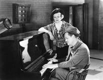 Άνδρας που παίζει το πιάνο ενώ μια γυναίκα ακούει (όλα τα πρόσωπα που απεικονίζονται δεν ζουν περισσότερο και κανένα κτήμα δεν υπ Στοκ Φωτογραφία
