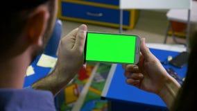 Άνδρας που παρουσιάζει στη γυναίκα και που κρατά το έξυπνο τηλέφωνο με την πράσινη οθόνη απόθεμα βίντεο