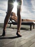 Άνδρας που στηρίζεται σε Deckchair και που εξετάζει τη γυναίκα Στοκ Φωτογραφία