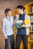 Άνδρας σπουδαστής με τα βιβλία που εξετάζει το φίλο μέσα Στοκ φωτογραφίες με δικαίωμα ελεύθερης χρήσης