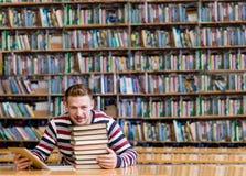 Άνδρας σπουδαστής με τον υπολογιστή ταμπλετών στη βιβλιοθήκη Στοκ Φωτογραφίες