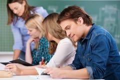Άνδρας σπουδαστής με τους συμμαθητές και το δάσκαλο στοκ φωτογραφία