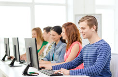 Άνδρας σπουδαστής με τους συμμαθητές στην κατηγορία υπολογιστών στοκ φωτογραφία