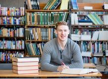 Άνδρας σπουδαστής πορτρέτου με το ανοικτό βιβλίο που λειτουργεί σε μια βιβλιοθήκη Στοκ φωτογραφία με δικαίωμα ελεύθερης χρήσης