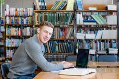 Άνδρας σπουδαστής πορτρέτου με το lap-top στην πανεπιστημιακή βιβλιοθήκη Στοκ Φωτογραφίες