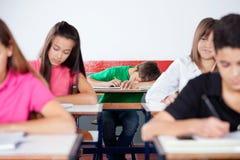 Άνδρας σπουδαστής που κοιμάται επάνω στην τάξη Στοκ Φωτογραφία