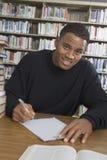 Άνδρας σπουδαστής που μελετά στη βιβλιοθήκη κολλεγίου Στοκ Φωτογραφία