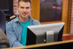 Άνδρας σπουδαστής που χρησιμοποιεί τον υπολογιστή στο δωμάτιο υπολογιστών Στοκ εικόνα με δικαίωμα ελεύθερης χρήσης