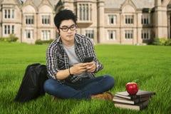 Άνδρας σπουδαστής που χρησιμοποιεί το κινητό τηλέφωνο υπαίθριο Στοκ Φωτογραφίες