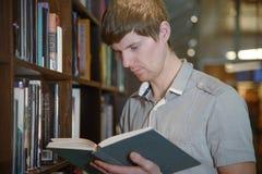 Άνδρας σπουδαστής σε μια βιβλιοθήκη Στοκ εικόνα με δικαίωμα ελεύθερης χρήσης