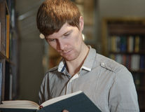 Άνδρας σπουδαστής σε μια βιβλιοθήκη Στοκ εικόνες με δικαίωμα ελεύθερης χρήσης