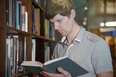 Άνδρας σπουδαστής σε μια βιβλιοθήκη Στοκ Φωτογραφία