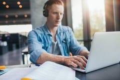 Άνδρας σπουδαστής στην πανεπιστημιακή βιβλιοθήκη που χρησιμοποιεί το lap-top Στοκ Φωτογραφία