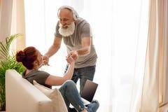 Άνδρας στα ακουστικά και γυναίκα με τα χέρια και το χαμόγελο εκμετάλλευσης lap-top του ενός τον άλλον Στοκ φωτογραφία με δικαίωμα ελεύθερης χρήσης