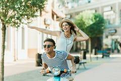 Άνδρας στα γυαλιά ηλίου και ευτυχής νέα γυναίκα αχύρου μοτοποδήλατο και το χαμόγελο καπέλων στο οδηγώντας στοκ φωτογραφίες