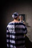 Άνδρας φυλακισμένος που στέκεται με την οδοντόβουρτσα και που εξετάζει το reflec του Στοκ Φωτογραφία