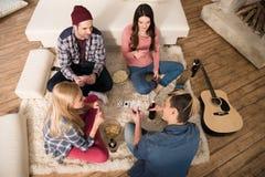 Άνδρες και γυναίκες που παίζουν τις κάρτες και που τρώνε popcorn στο σπίτι Στοκ εικόνες με δικαίωμα ελεύθερης χρήσης