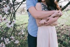 Άνδρες και η γυναίκα χεριών οι νεαροί που αγκαλιάζουν ένα όμορφο κορίτσι στην άνθιση καλλιεργούν, Στοκ φωτογραφίες με δικαίωμα ελεύθερης χρήσης