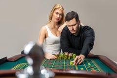 Άνδρες με τις γυναίκες που παίζουν τη ρουλέτα στη χαρτοπαικτική λέσχη Στοκ Εικόνες