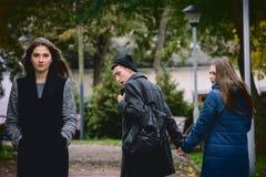 Άπιστο άτομο με τη φίλη του και την εξέταση κατάπληκτος ένα άλλο σαγηνευτικό κορίτσι Στοκ Φωτογραφία