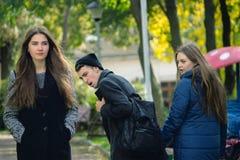 Άπιστο άτομο που περπατά με τη φίλη και που εξετάζει κατάπληκτο ένα άλλο σαγηνευτικό κορίτσι Στοκ Εικόνα